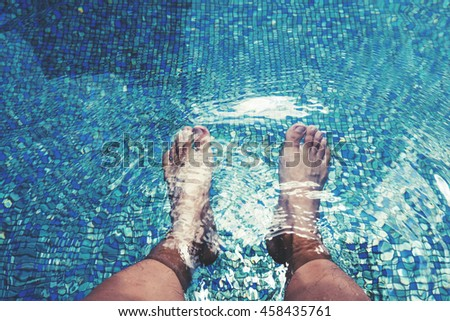 Male feet with skin tan, dipping in swimming pool - stock photo