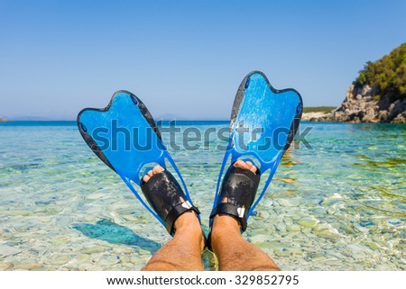Male feet with snorkeling fins in the shores of the mediterranean sea. - stock photo