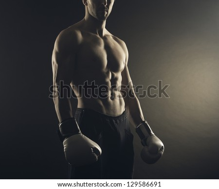 Male fighter posing in front of a dark background - stock photo