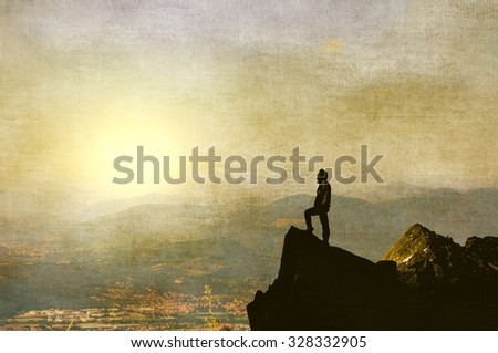 Male figure on top of the mountain in evening with far view - stock photo