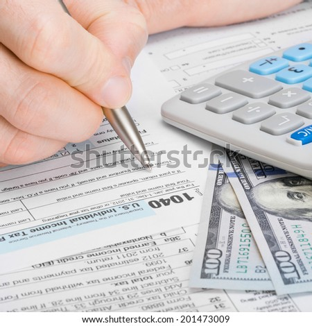Male filling out 1040 United States of America Tax Form - 1 to 1 ratio - stock photo