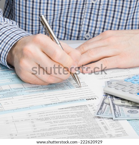 Male filling out 1040 US Tax Form - 1 to 1 ratio - stock photo