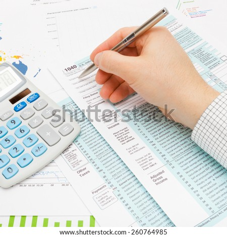 Male filling out 1040 US Tax Form using silver ball pen - studio shot - stock photo