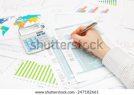 Male filling out 1040 US Tax Form with silver ball pen - stock photo