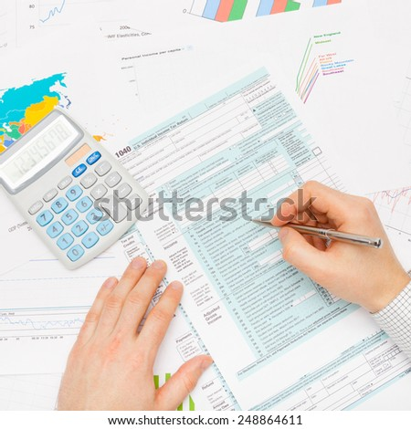 Male filling out 1040 US Tax Form with silver pen - studio shot - stock photo