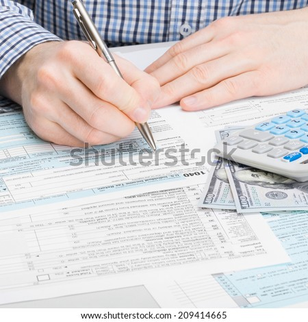 Male filling out 1040 USA Tax Form - studio shoot - 1 to 1 ratio - stock photo