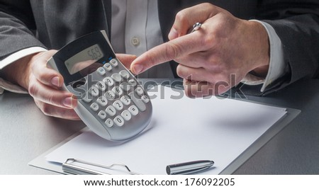 male financial manager displaying figures on calculator - stock photo