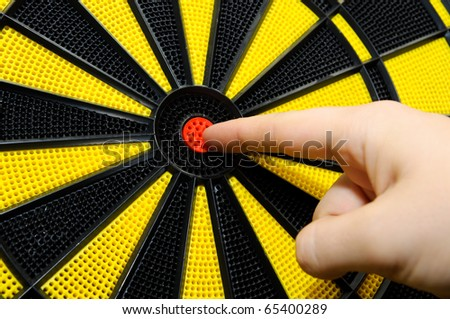Male finger showing bulls eye on dart game board - stock photo