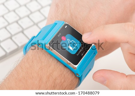 Male finger taps like icon on blue smart watch - stock photo