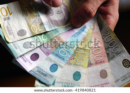 Male fingers holding various banknotes of Serbian dinar currency money. - stock photo