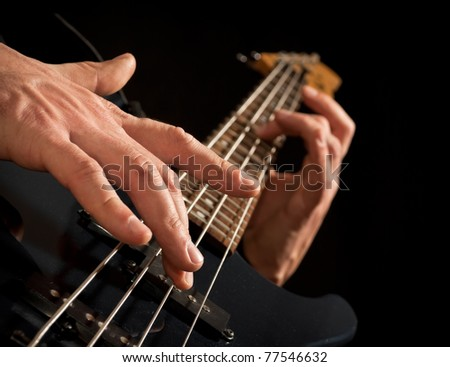 male fingers playing on electrical bass guitar - stock photo