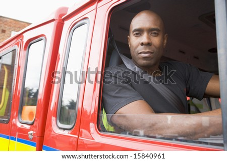 Male firefighter sitting in the cab of a fire engine - stock photo
