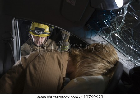 Male firefighter trying to open car's door - stock photo