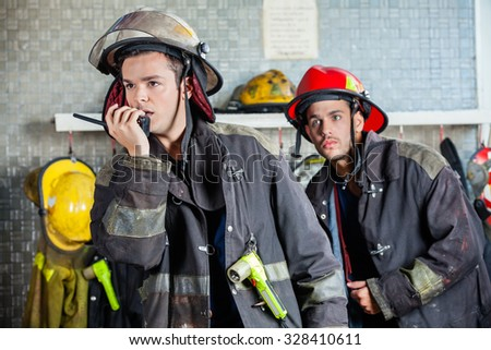 Male firefighter using walkie talkie at fire station with colleague standing in background - stock photo