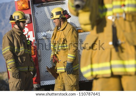 Male firefighters talking with each other with colleague in the foreground - stock photo