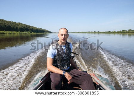male fisherman on  boat is moving over a large river