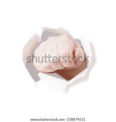 male fist punching hole through paper wall - stock photo