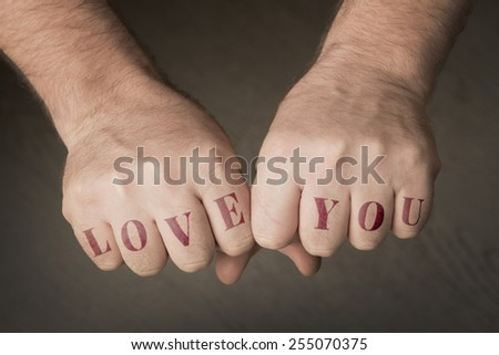 "Male fist with the words ""Love you"""