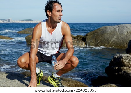 Male fit runner resting while sitting on rocks with blue sea on background, attractive runner holding bottle of water taking a break after workout, man resting after doing sports outdoors - stock photo