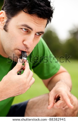 Male fitness coach blowing whistle - stock photo