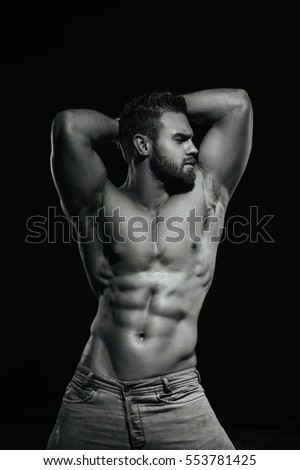 Male fitness model Konstantin Kamynin posing shirtless on black background with hands up