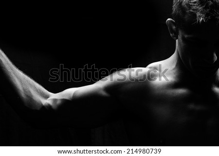 Male fitness model showing muscles in studio with a black background - stock photo