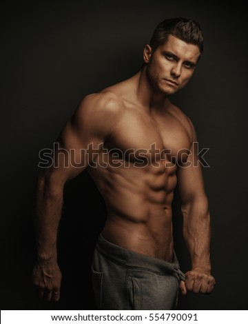 Male fitness model standing on black background with holding his pant's ropes