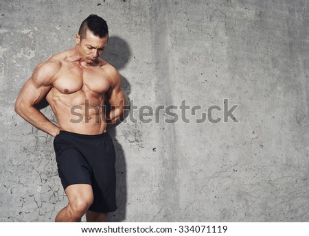 Male fitness model with abdominal muscles standing on grey background with room for text copy space.
