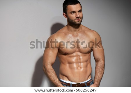 Male Fitness Model With Sexy Muscular Body Portrait. Handsome Hot Young Man With Fit Athletic Body Shape, Perfect Abs Muscles And Naked Torso On Grey Background. Bodybuilding Concept. High Resolution