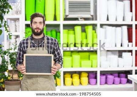 Male florist Holding an blank chalkboard - stock photo