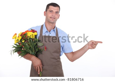 Male florist pointing out of shot