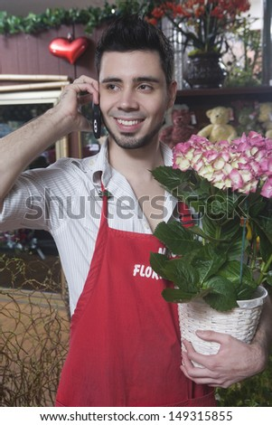 Male florist using mobile phone while holding hydrangea plant in shop - stock photo