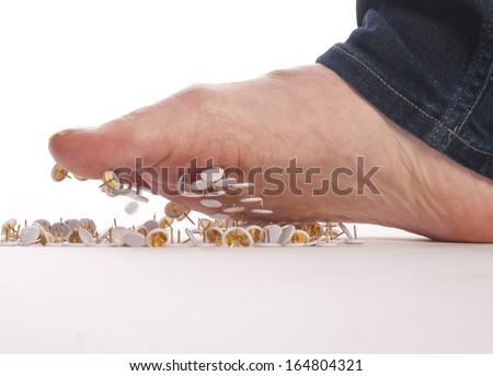 male foot above pushpin - stock photo