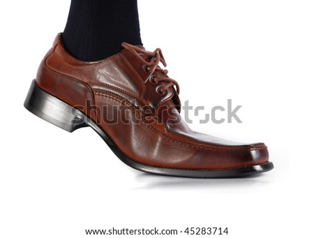 Male foot in brow shoe walking on white background