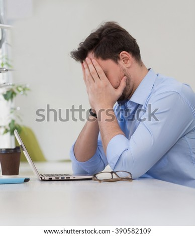 Male freelancer closing his face and sitting in front of laptop computer while working in restaurants with business projects.