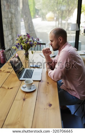 Male freelancer connecting to wireless via laptop computer, thoughtful businessman work on net-book while sitting at wooden table in modern coffee shop interior, student reading text or book in cafe - stock photo