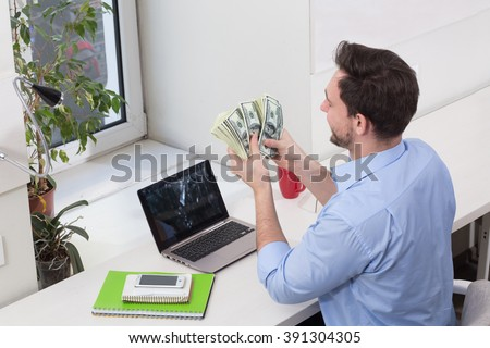 Male freelancer counting dollars in office while working on laptop computer. Handsome man looking on money. - stock photo