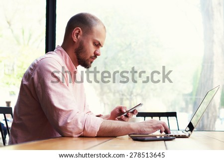 Male freelancer use notebook sitting in modern loft interior with big windows, confident business man busy using laptop at office desk, young student typing on computer while sitting at wooden table - stock photo