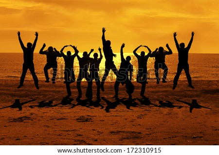 Male friends are having fun at summer and jumping up on the sunset near the sea putting their hands up to the orange sky - stock photo