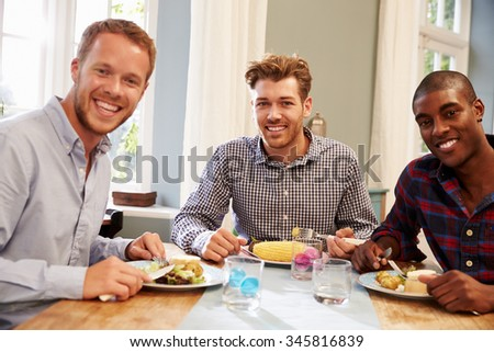 Male Friends At Home Sitting Around Table For Dinner Party - stock photo