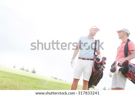 Male friends conversing at golf course against clear sky on sunny day - stock photo