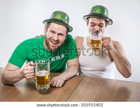 Male friends drinking on Saint Patrick's Day from large mugs of lager in green hats, wife beater, shirt, at favorite tavern having a good time - stock photo