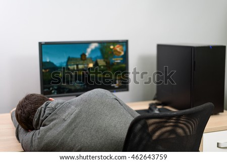 male gamer sleeping in front of computer after playing video games - stock photo