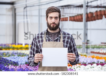 Male Garden Worker Holding an Open Signboard - stock photo