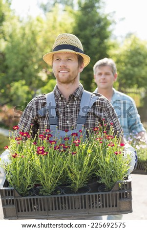 Male gardeners carrying flower pots in crates at plant nursery - stock photo