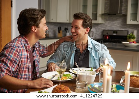 Male gay couple having a romantic dinner in their kitchen - stock photo