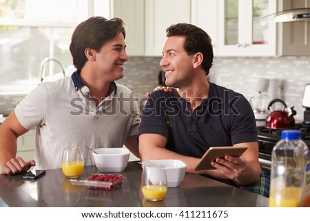 Male gay couple in kitchen with tablet looking at each other - stock photo