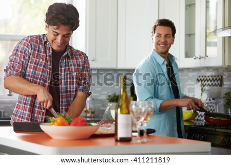Male gay couple preparing a meal together in the kitchen - stock photo
