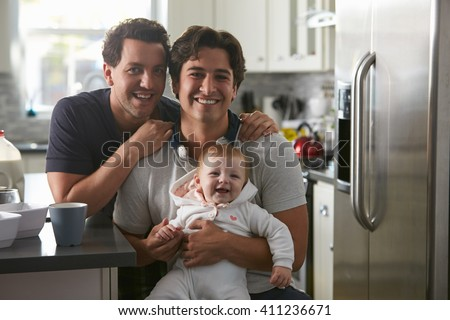 Male gay couple with baby girl in kitchen looking to camera - stock photo
