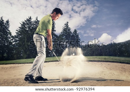 Male golf player in green shirt and grey pants hitting golf ball out of a sand trap with sand wedge and sand caught in motion. - stock photo